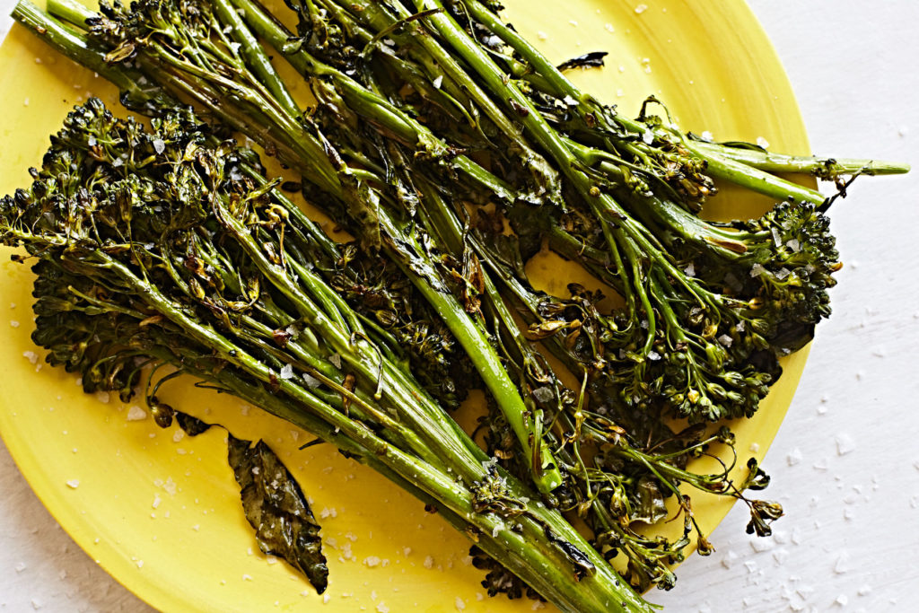 Roasted broccolini on a yellow plate