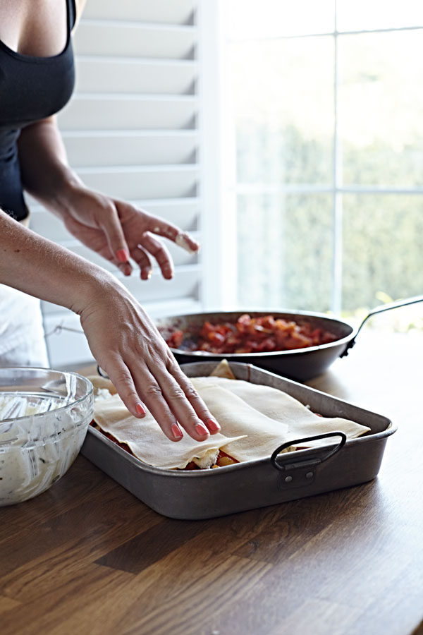 Woman assembling a vegetable lasagna with homemade noodles.