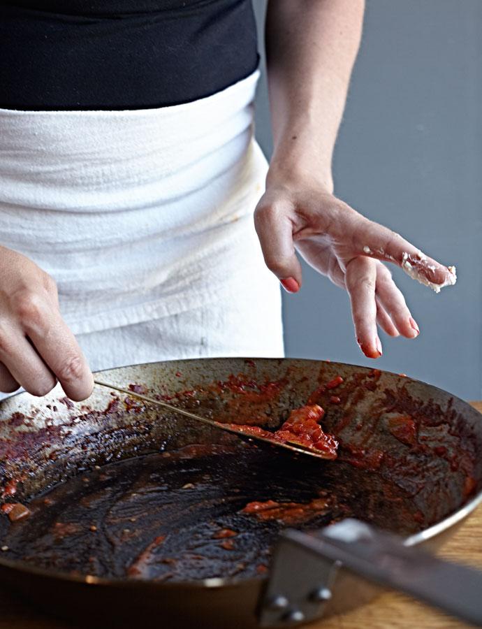 Woman spooning vegetable sauce.