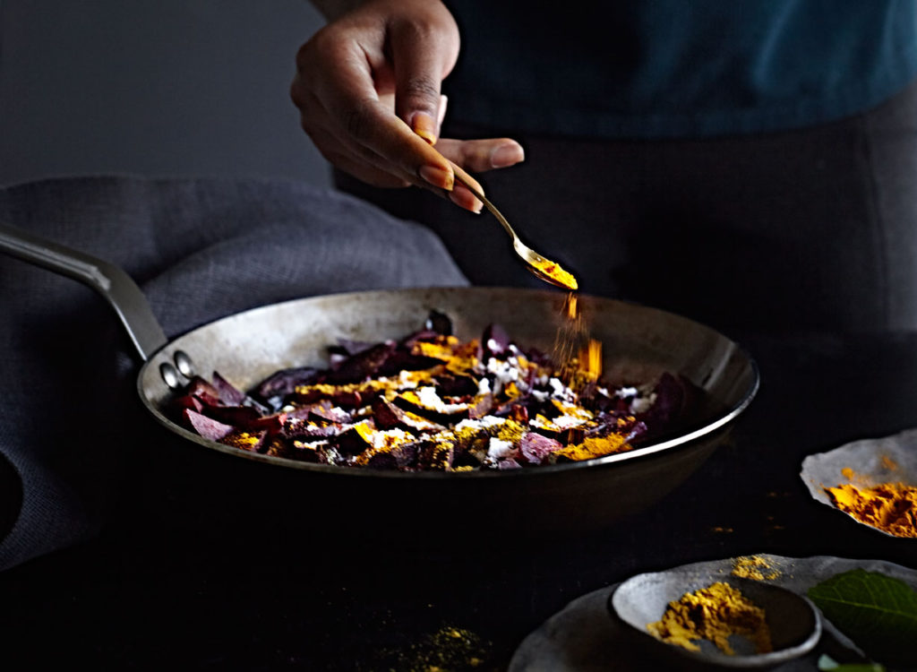 Dark-skinned woman's hand sprinkling turmeric over pan of beet curry.