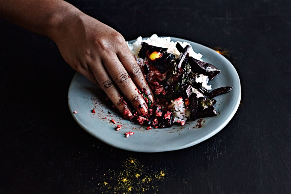 Dark-skinned woman eating Sri Lankan beet curry with her hand.