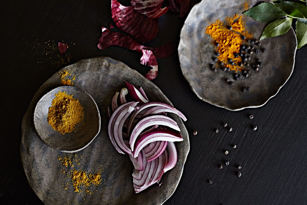 Turmeric, red onion, curry powder and peppercorn ingredient shot on dark handmade dishes.