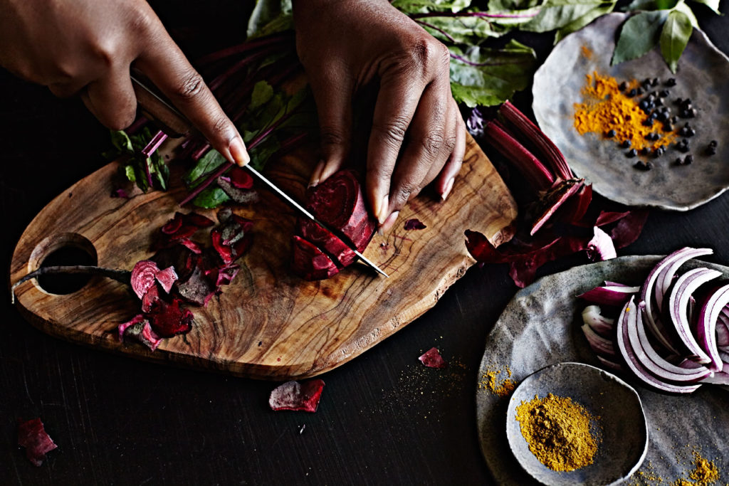 Dark-skinned woman's hands slicing red beets.