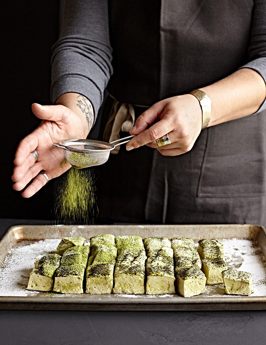 Woman's hand sprinkling matcha powder over homemade green tea matcha marshmallows.