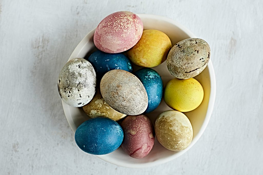 Eggs naturally dyed with foods in bowl.