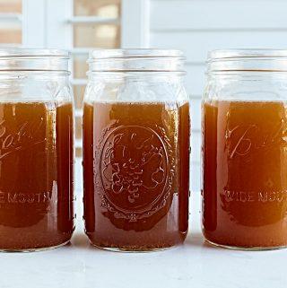 Jars of homemade nourishing bone broth on a countertop.