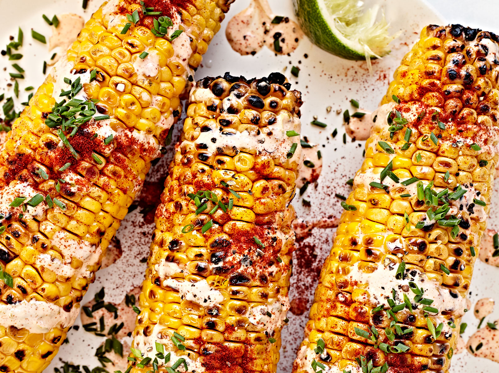 Close up of mexican street corn with cheese, herbs and chili powder.