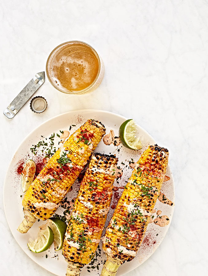 Mexican street corn with cheese, herbs and chili powder.