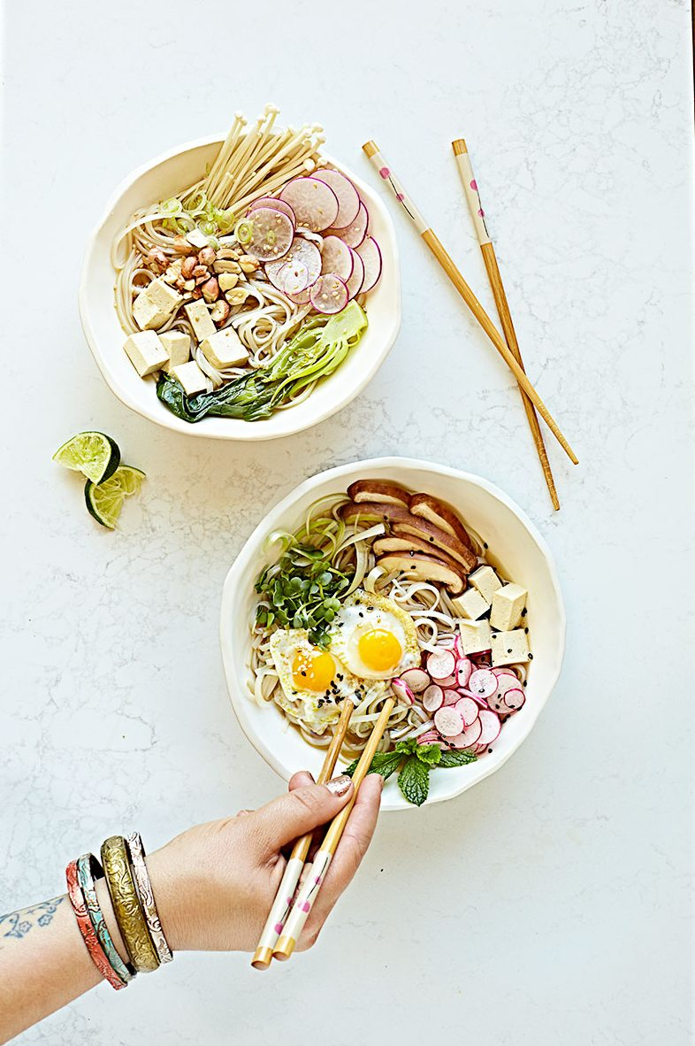 Two bowls of vegetarian pho noodle soup with different toppings and a hand reaching in to eat it.