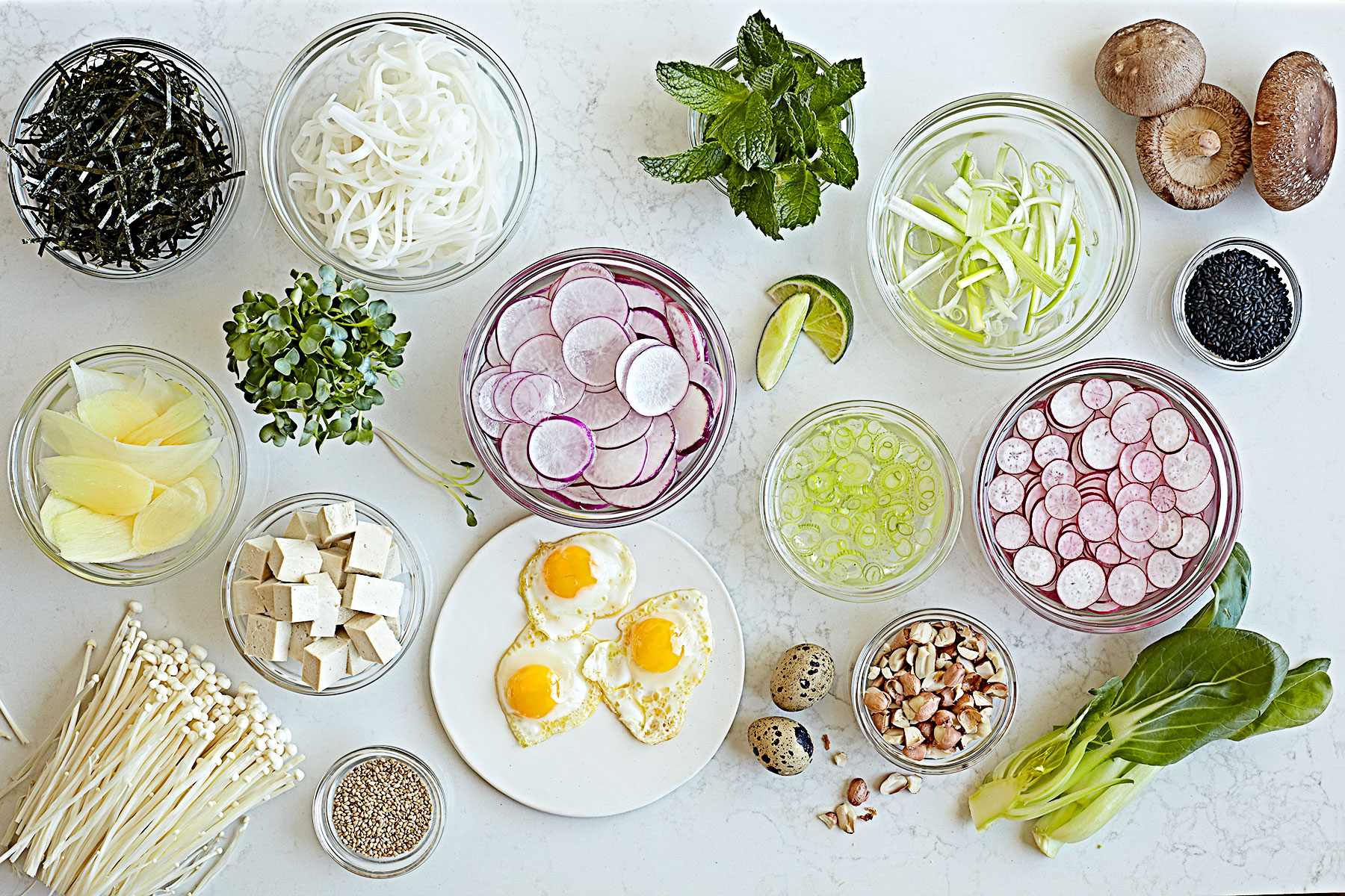 A spread of toppings for pho noodle soup including quail eggs, radishes, tofu, mushrooms, and sprouts.