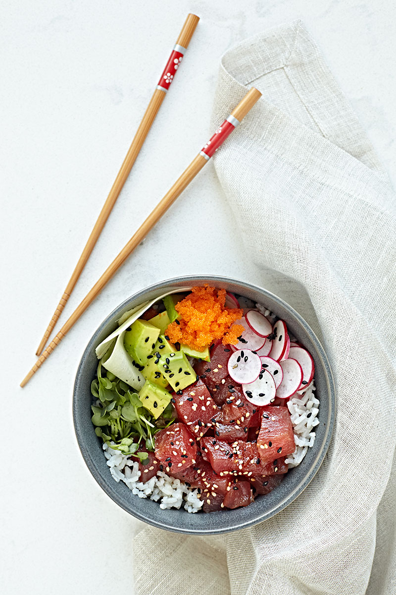 Ahi tuna poke bowl with avocado, radishes, masago, ginger, and sprouts over coconut rice.