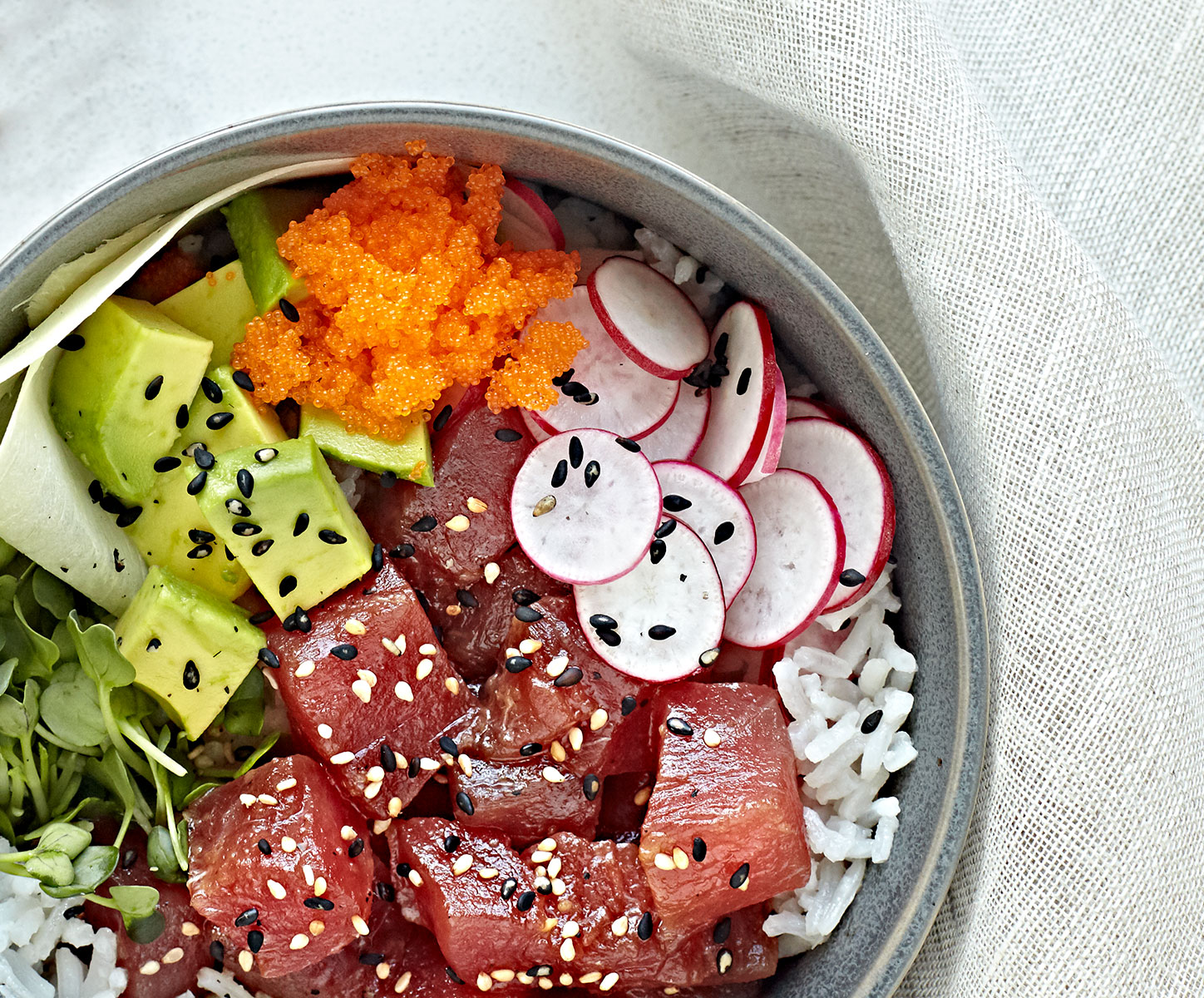 Close up of ahi tuna poke bowl with avocado, radishes, masago, ginger, and sprouts over coconut rice.