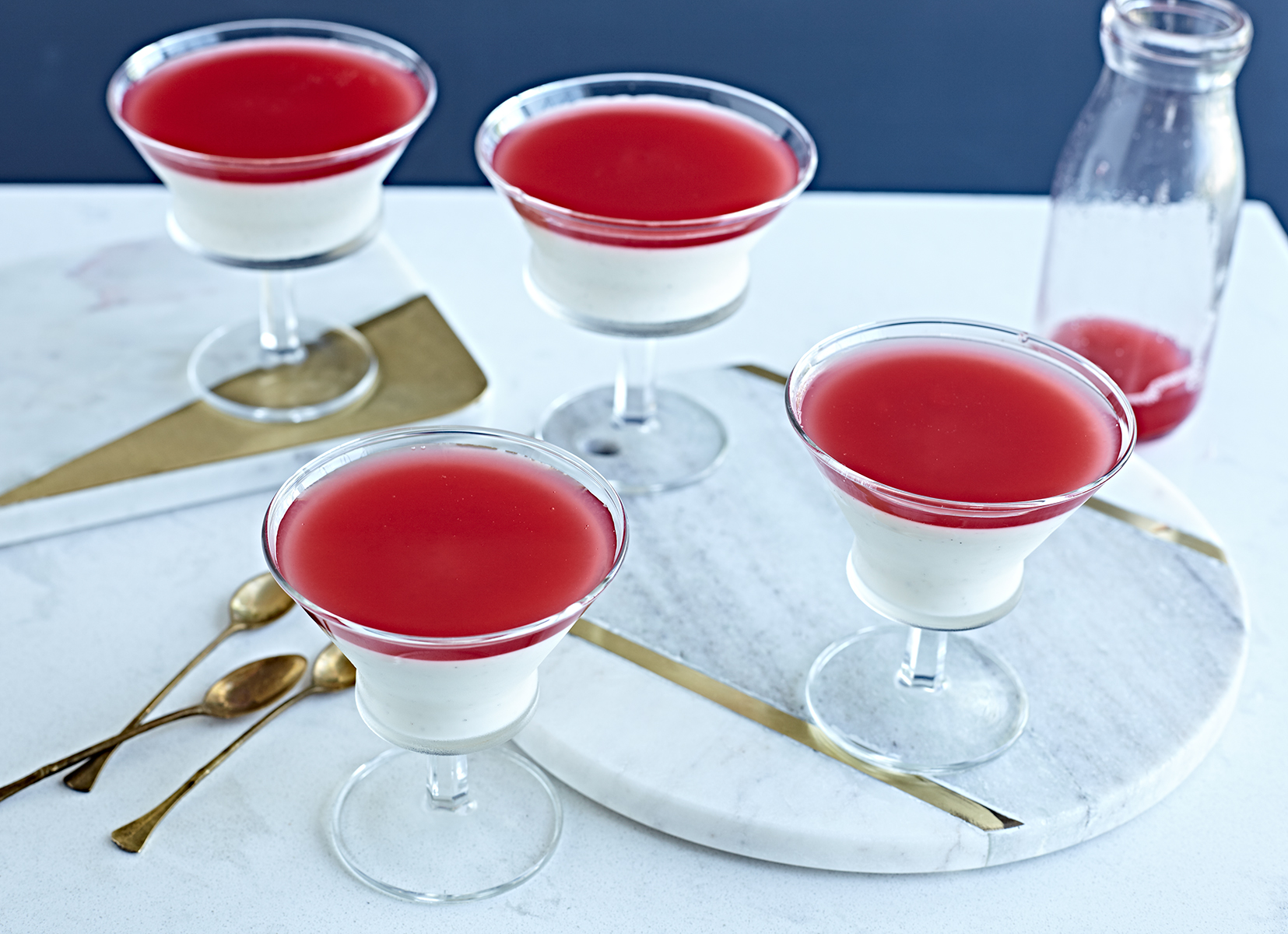 Fancy glasses of yogurt panna cotta with rhubarb syrup and gold spoons.