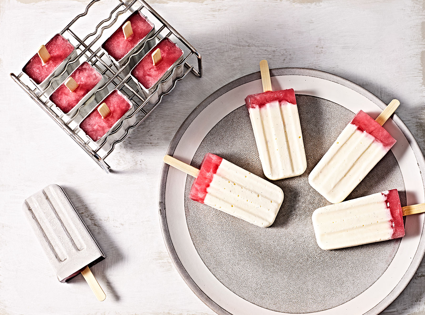 Creamy cheesecake rhubarb popsicles in a mold and on a plate.