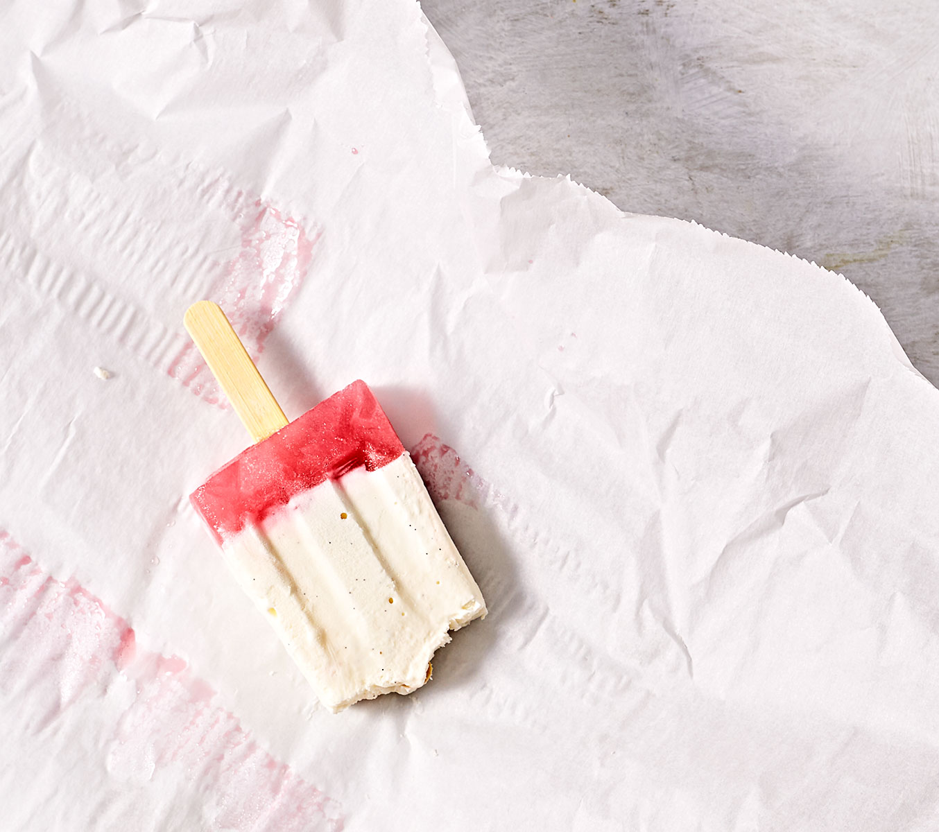 Creamy cheesecake rhubarb popsicle with bites taken out.