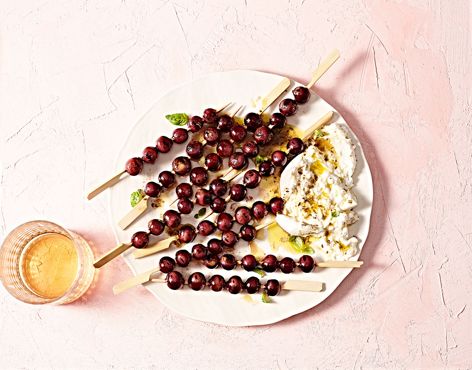 Char grilled grapes in a tangy Vinaigrette with Burrata on a plate.