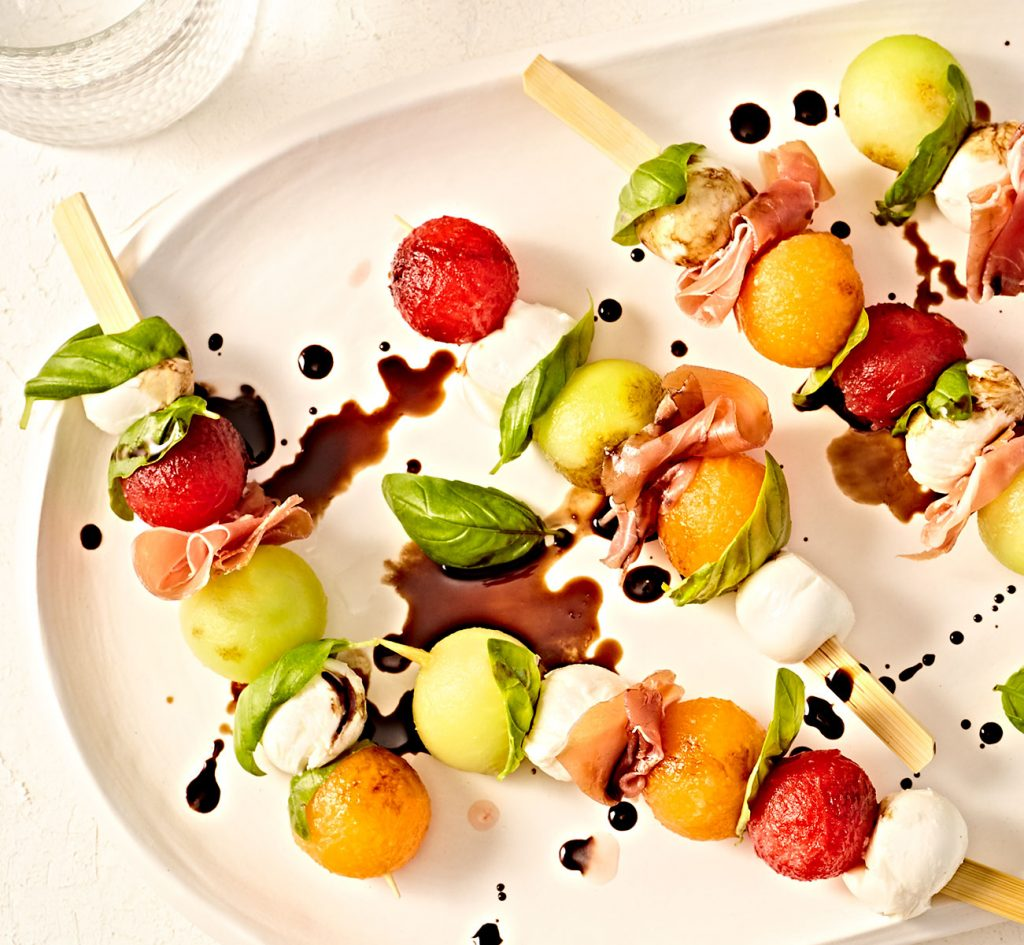 Mozzarella, prosciutto and melon skewers with basil on a serving dish.