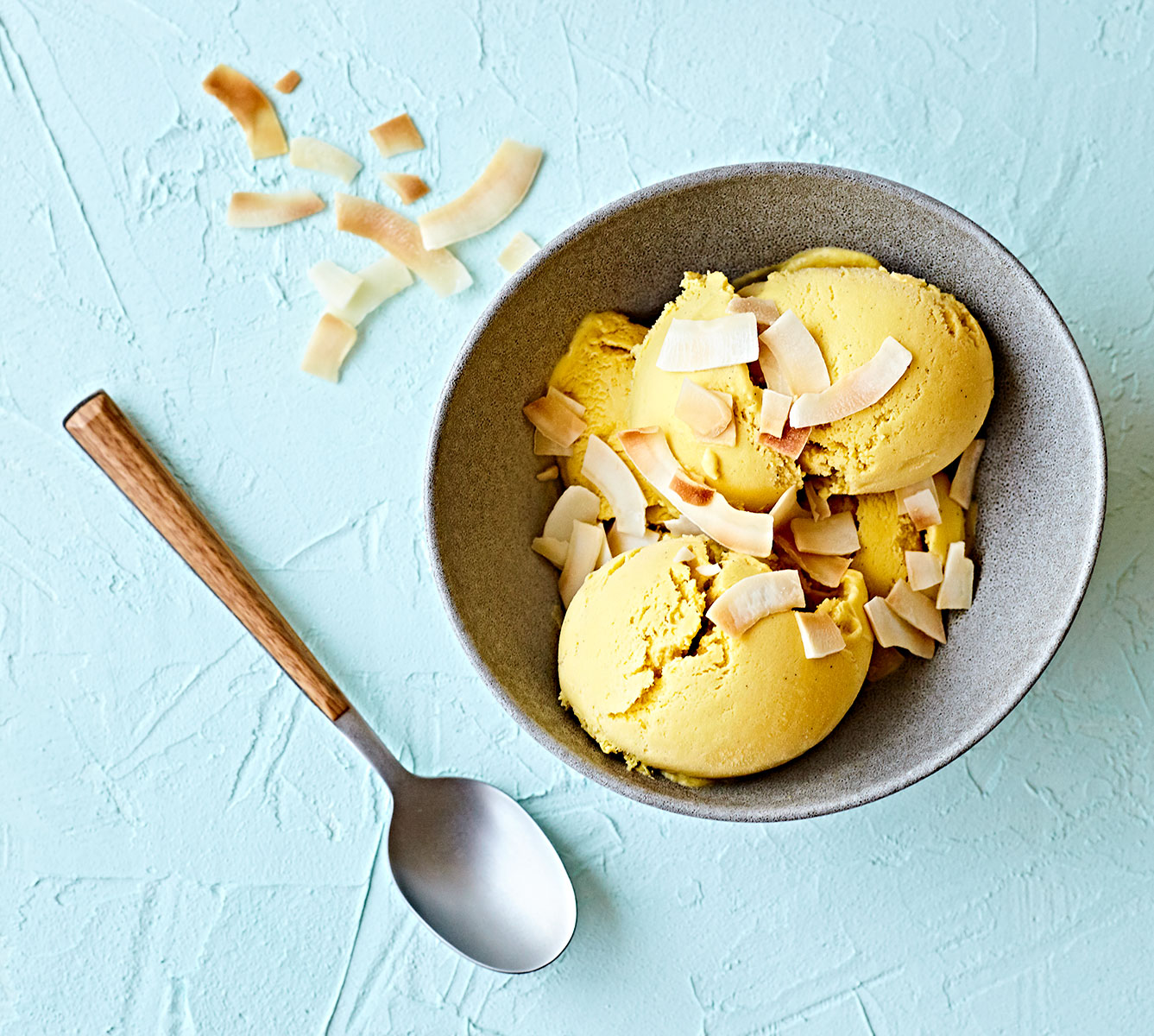 Mango coconut cream ice cream with roasted coconut in a bowl on a blue plaster table top.