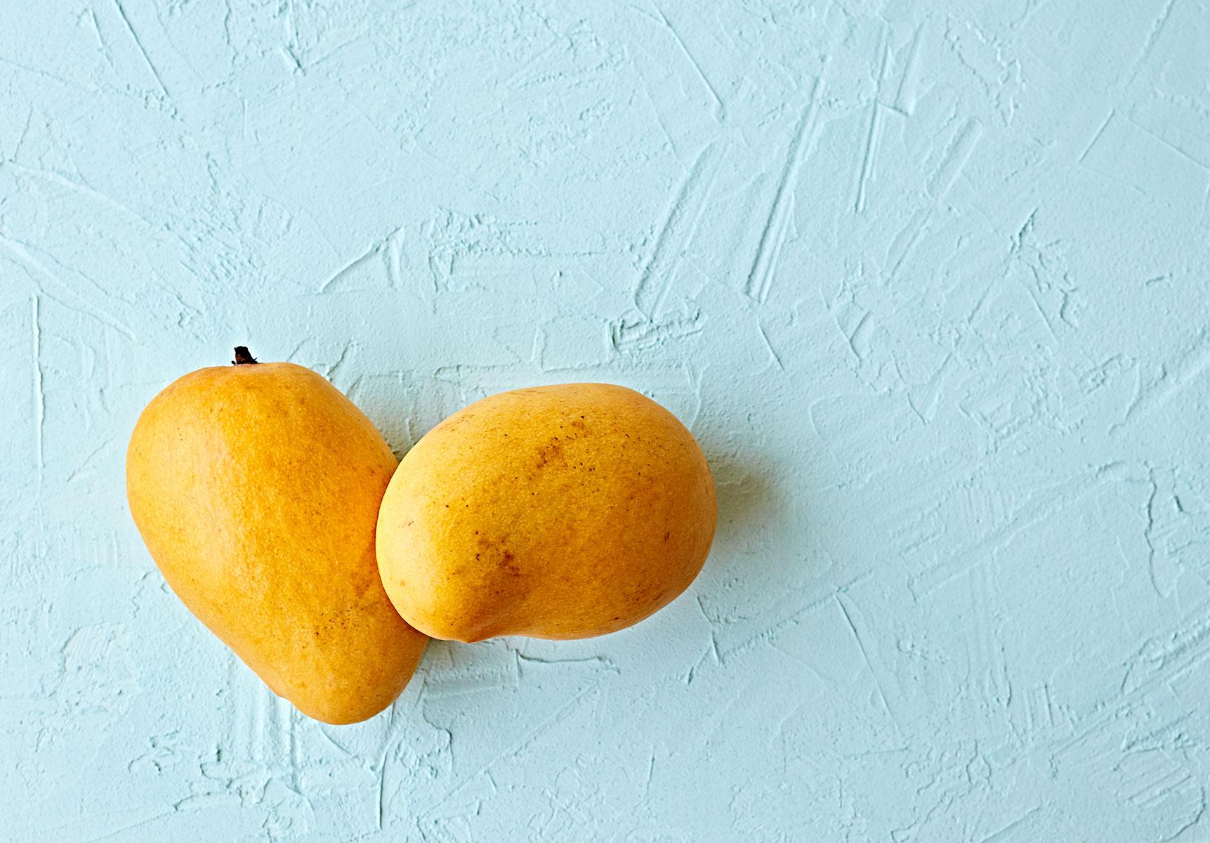 Alphonso mango on blue plaster table top.