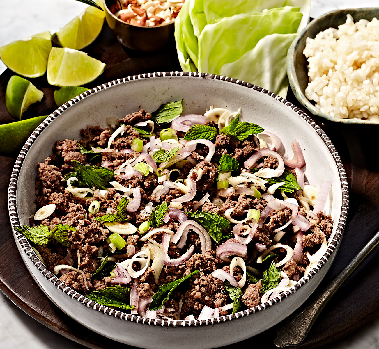 Thai beef larb in a bowl with cabbage, peanuts, lime and coconut sticky rice.