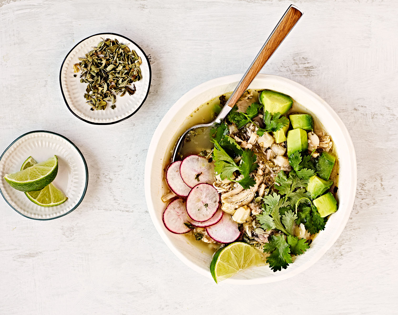 Overhead image of chicken pozole verde soup with lime, avocado, radishes and cilantro.