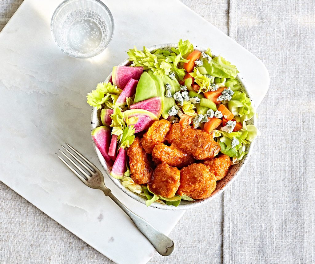 Gluten-free baked buffalo chicken tender salad with watermelon radishes, celery, avocado, and blue cheese.