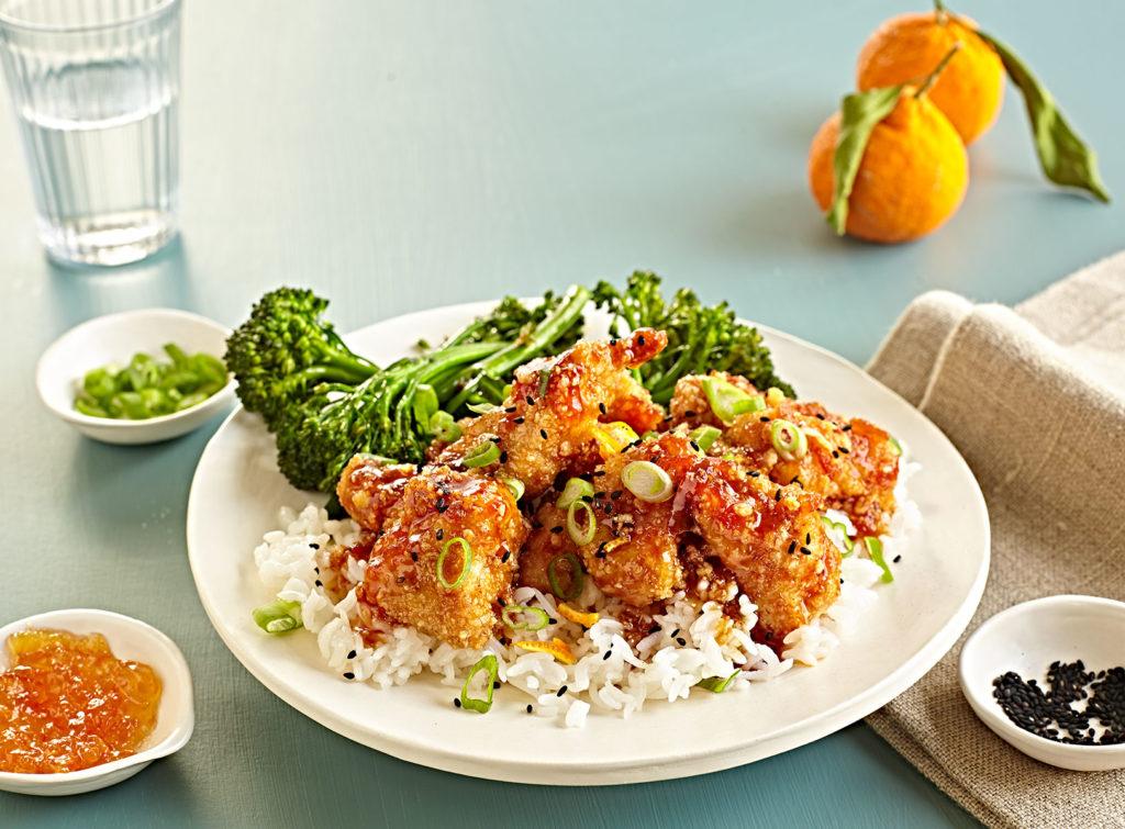 Gluten-free crispy orange chicken over rive with broccolini.