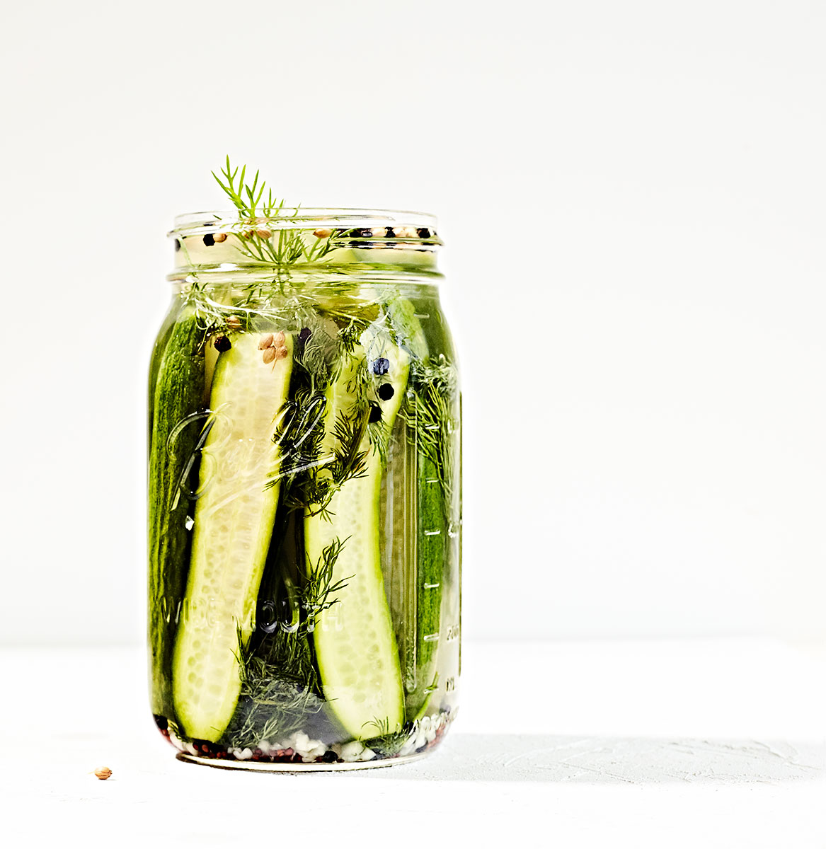 Quick refrigerator pickles in a jar with ingredients.