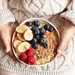 A child's hands holding vegan quinoa and oat overnight porridge topped with almond butter, berries, bananas, and honey.