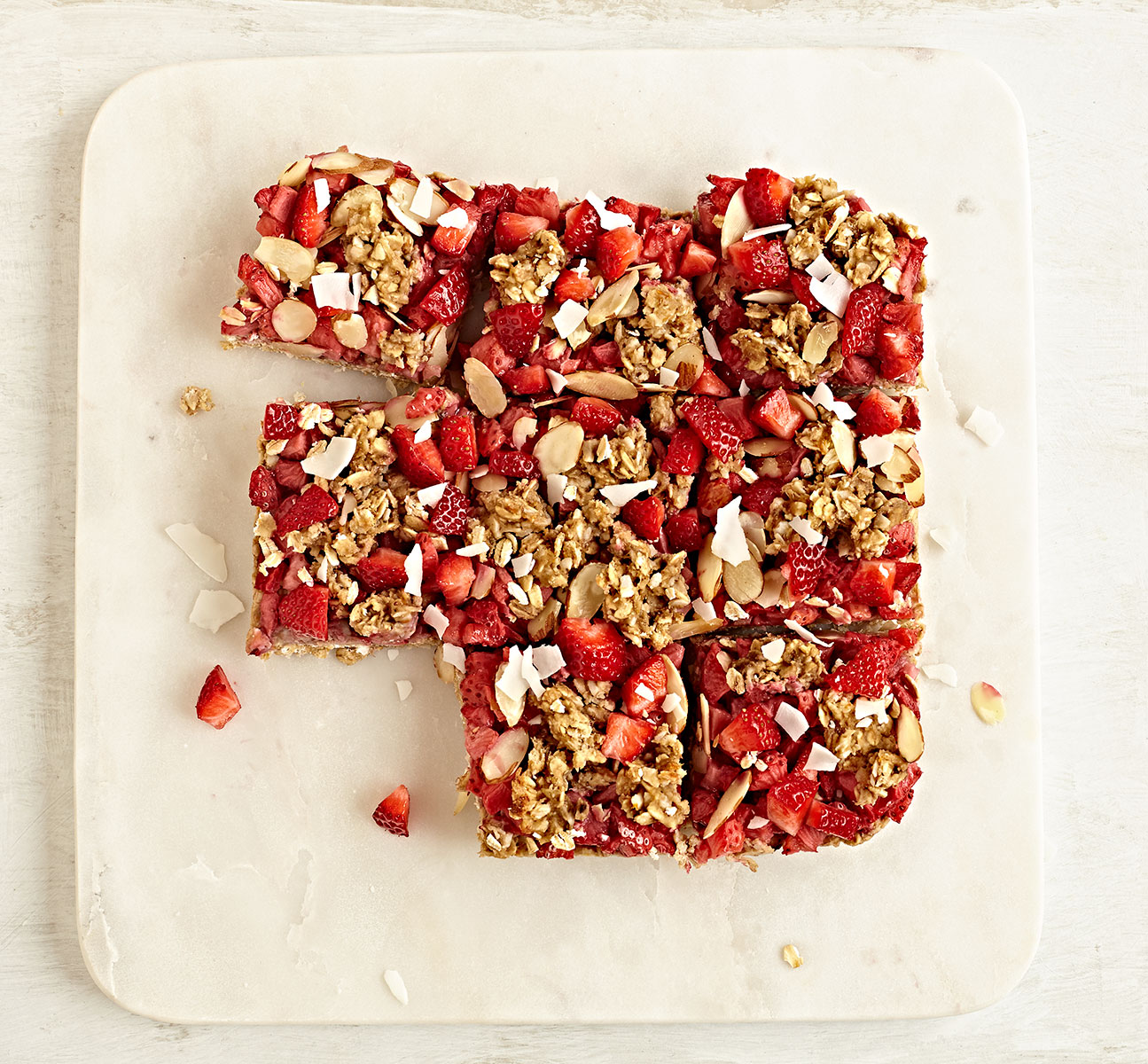 Gluten-free strawberry breakfast bars with almonds, oats, and coconut on marble board.
