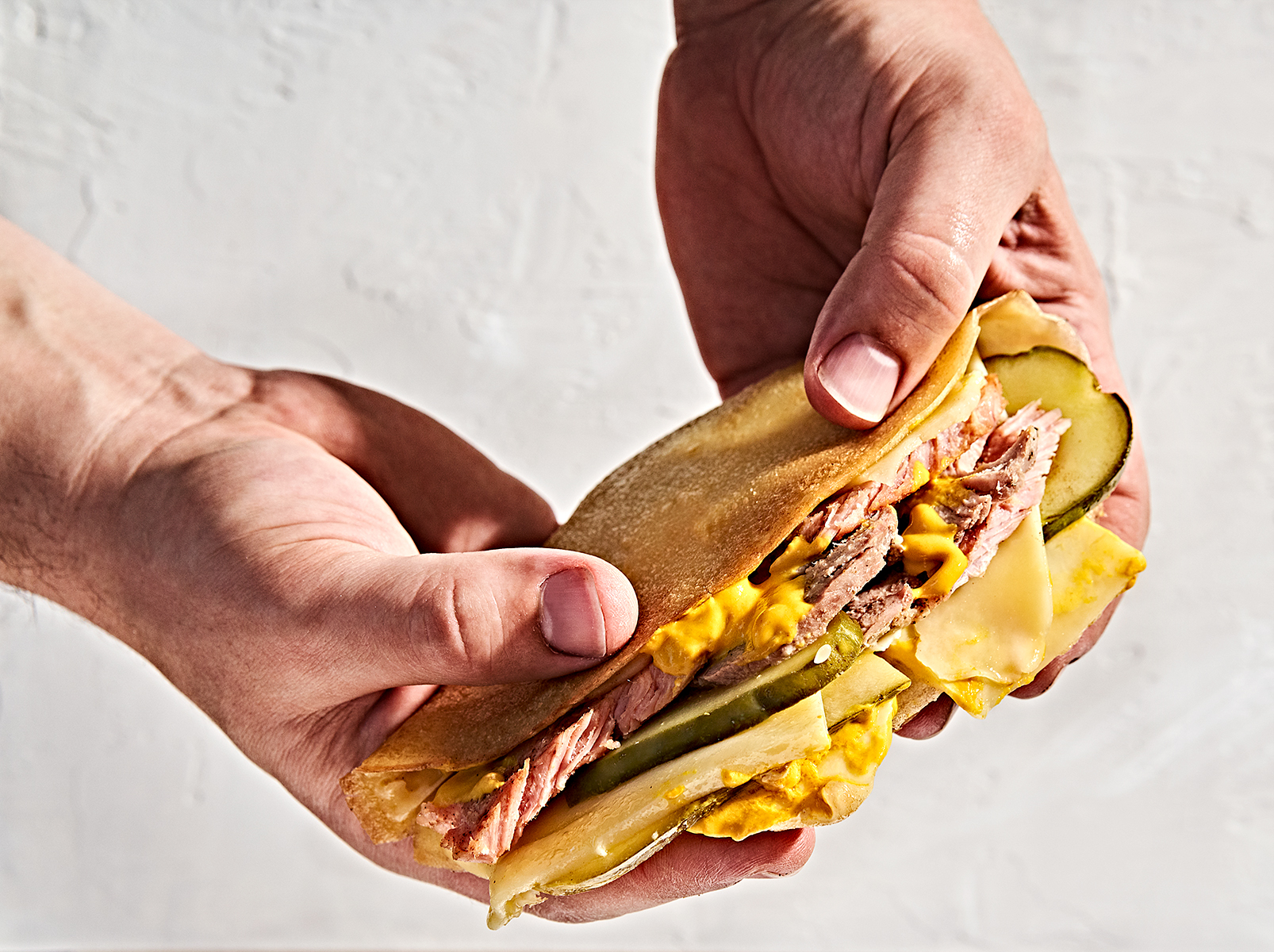 Man's hands holding a pressed gluten-free crepe cuban sandwich with ham, pork, mustard and pickles.