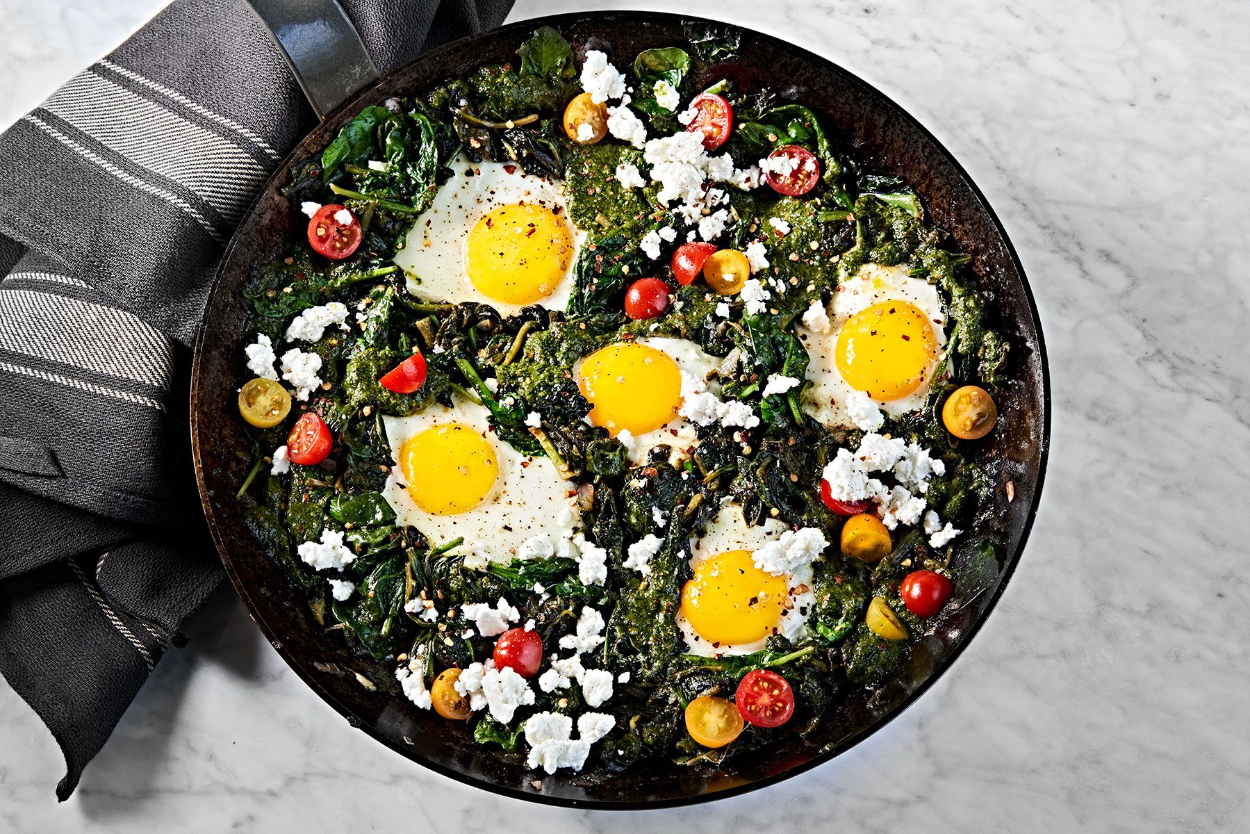 Green spinach and kale shakshuka with sunny-side up eggs and feta.