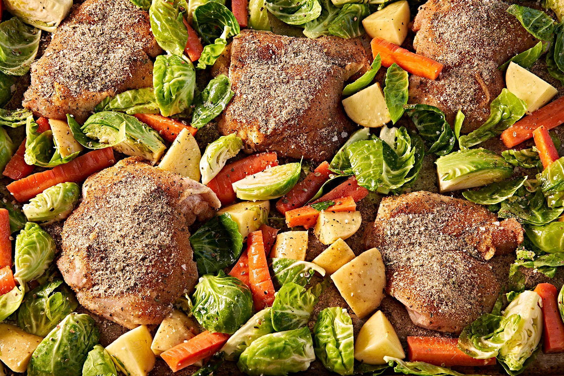 Seasoned raw chicken thighs ready roast in a sheet pan with vegetables.