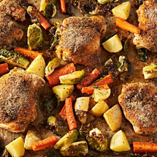 Roasted seasoned chicken thighs, carrots, potatoes and brussel sprouts in a sheet pan.