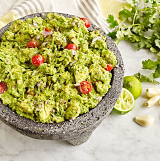 Authentic fresh guacamole with tomatoes made in a mocaljete.