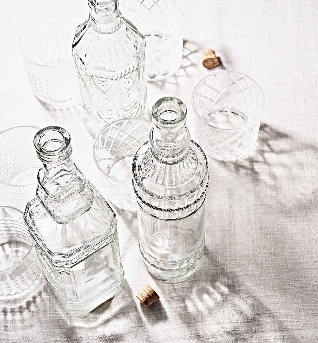 Glassware with shadows on a linen table.