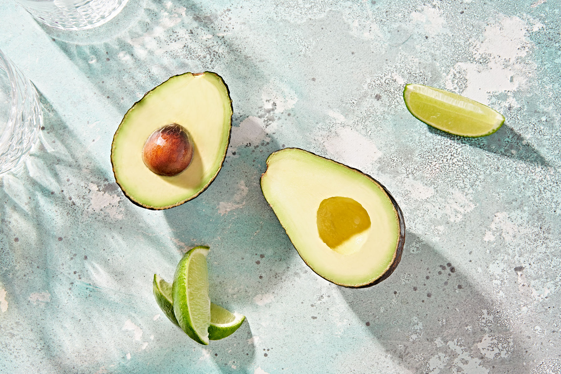 Overhead view of a perfect halved avocado and fresh lime wedges.