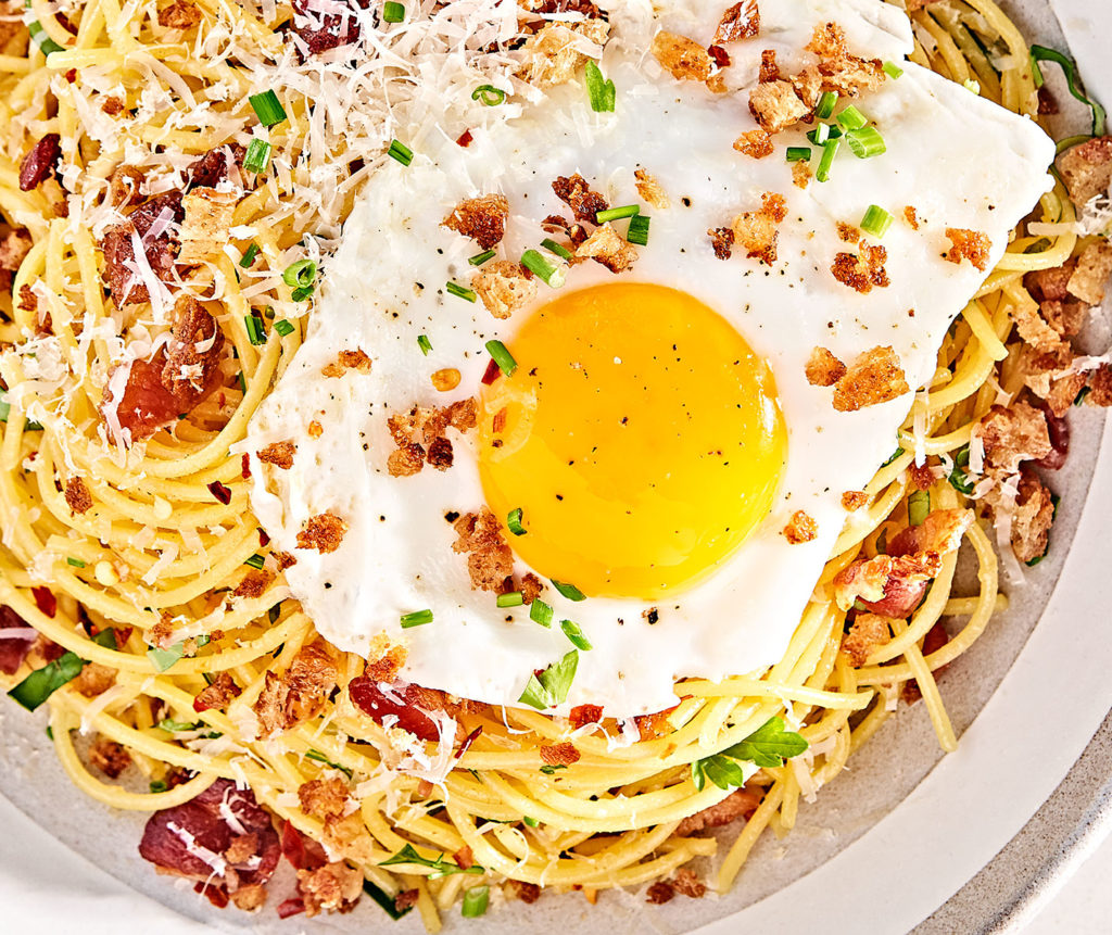 Close-up of Breakfast pasta with a sunny-side up egg.