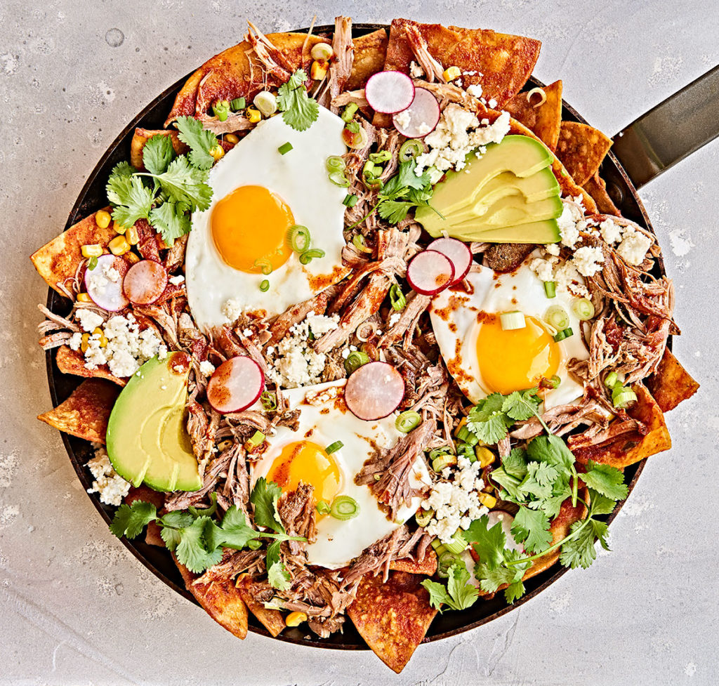 Chilaquiles breakfast with sunny-side egg in skillet.