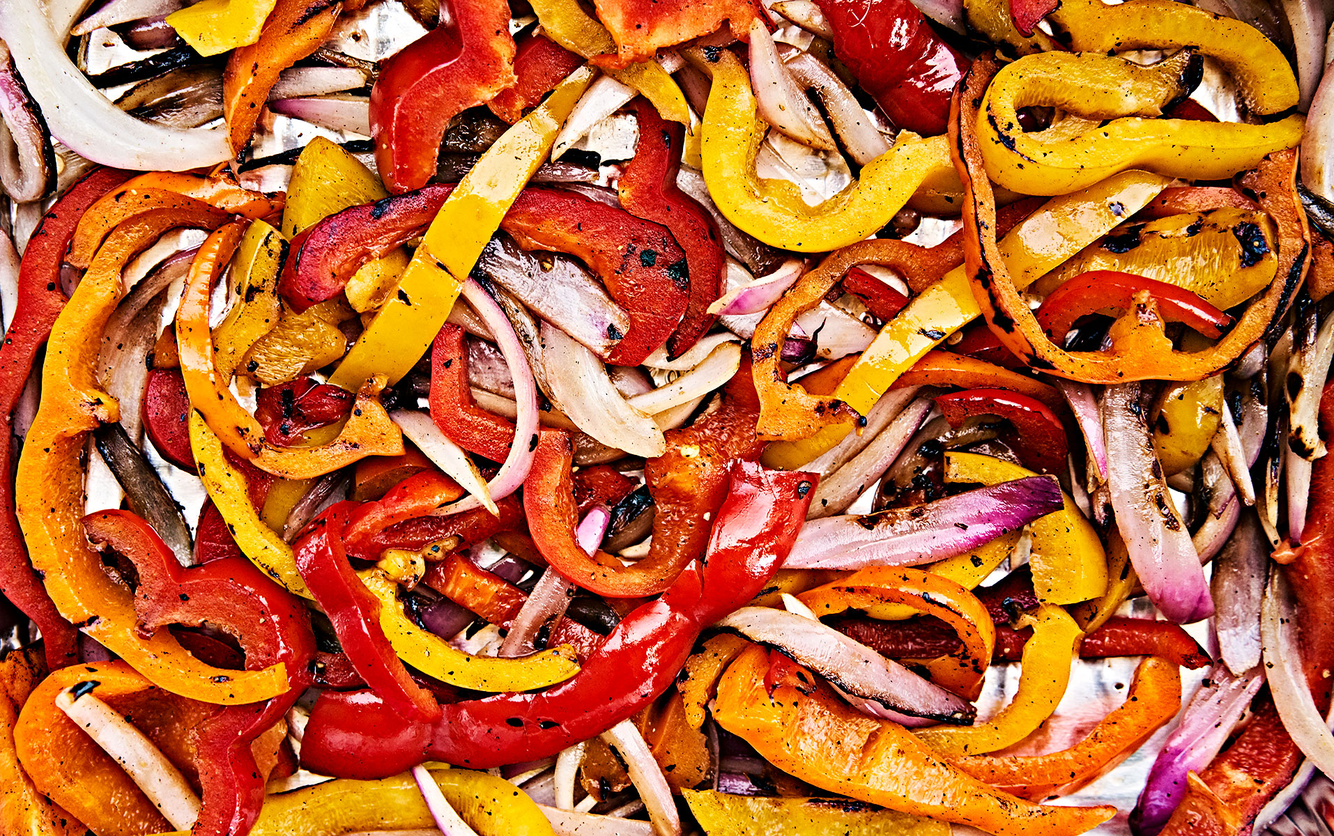 Sautéed red onions and bell peppers close-up.