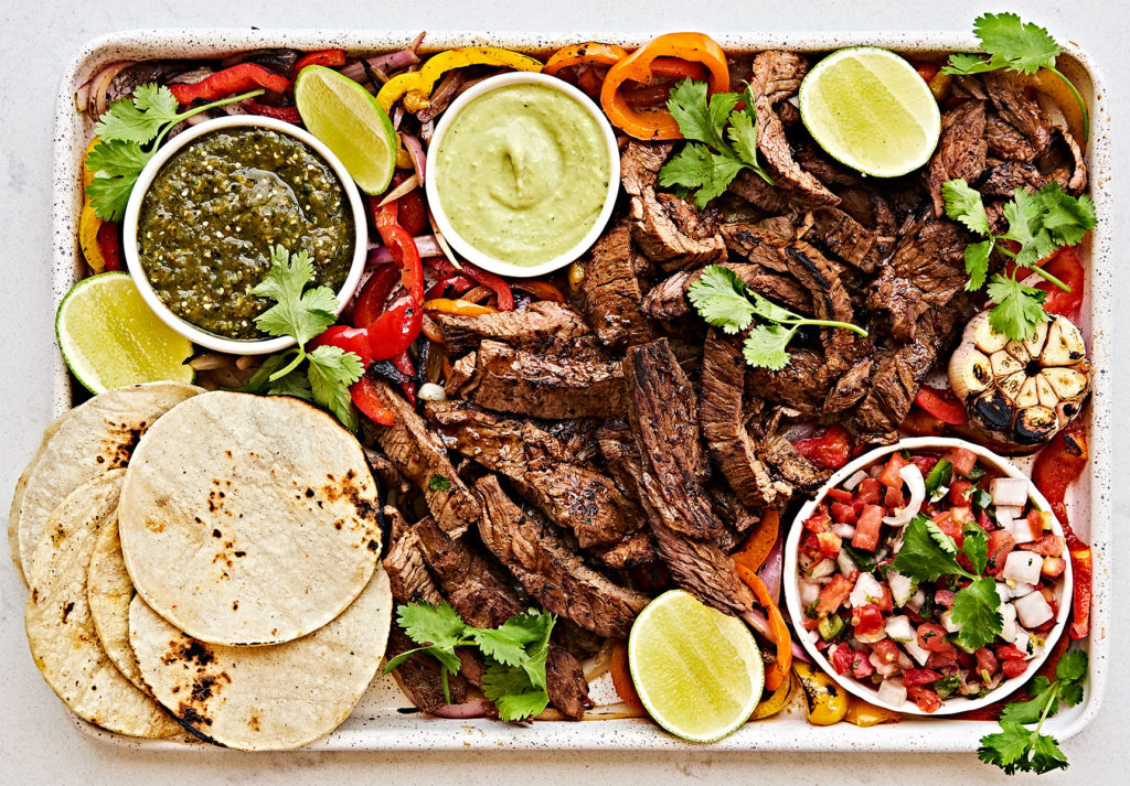 Platter of of steak fajitas flank steak with salsa verde, avocado crema, and street tortillas.