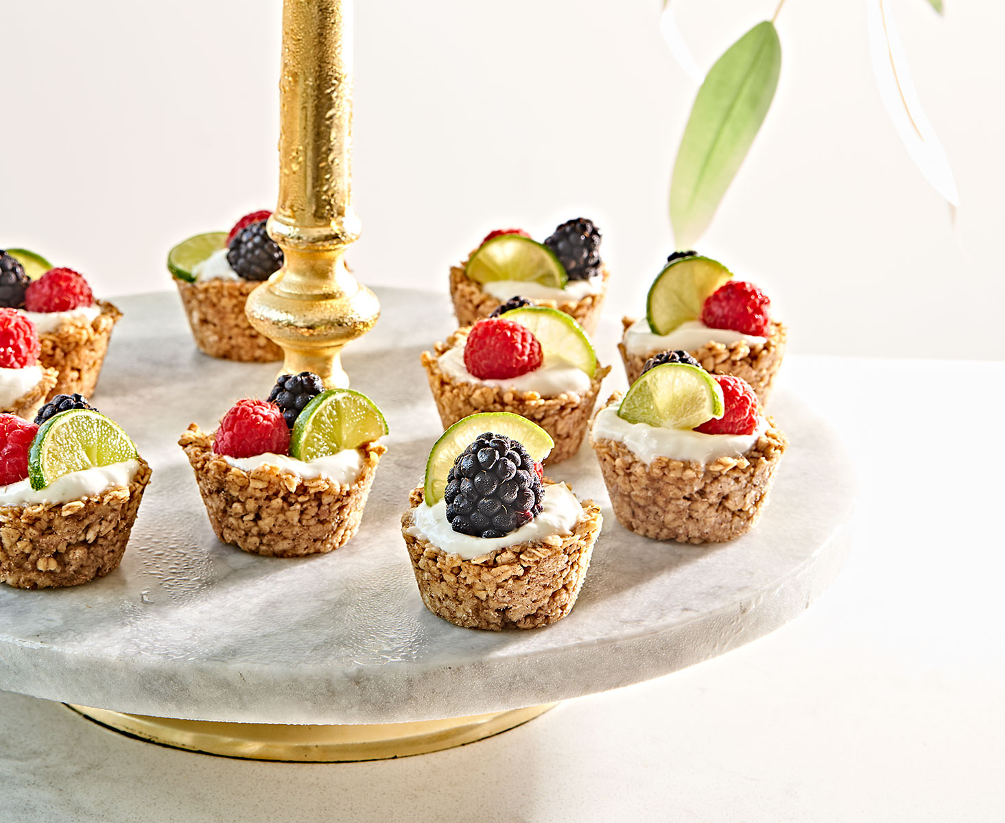 Bite-sized granola yogurt cups with berries and lime on two tiered stand.