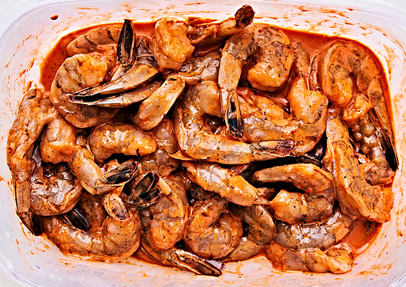 Close-up of marinated raw shrimp with the tails on.