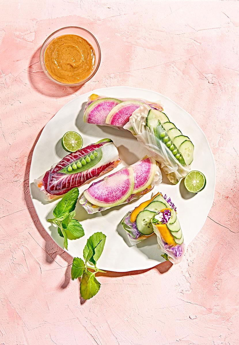 Vegan rainbow spring rolls with watermelon radish, pea pods, and mango on white plate.