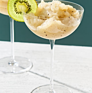 Kiwi slush margarita in stemmed glass garnished with kiwi slice.