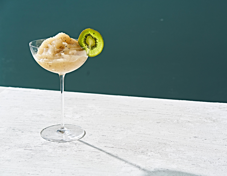 Kiwi slush margarita in stemmed glass garnished with kiwi slice.