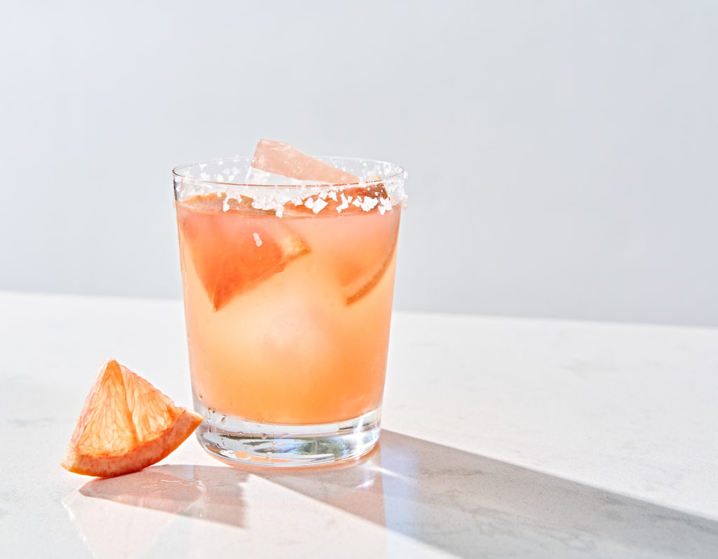 Salty chihuahua grapefruit and tequila margarita with salted rim and grapefruit garnish on marble table.