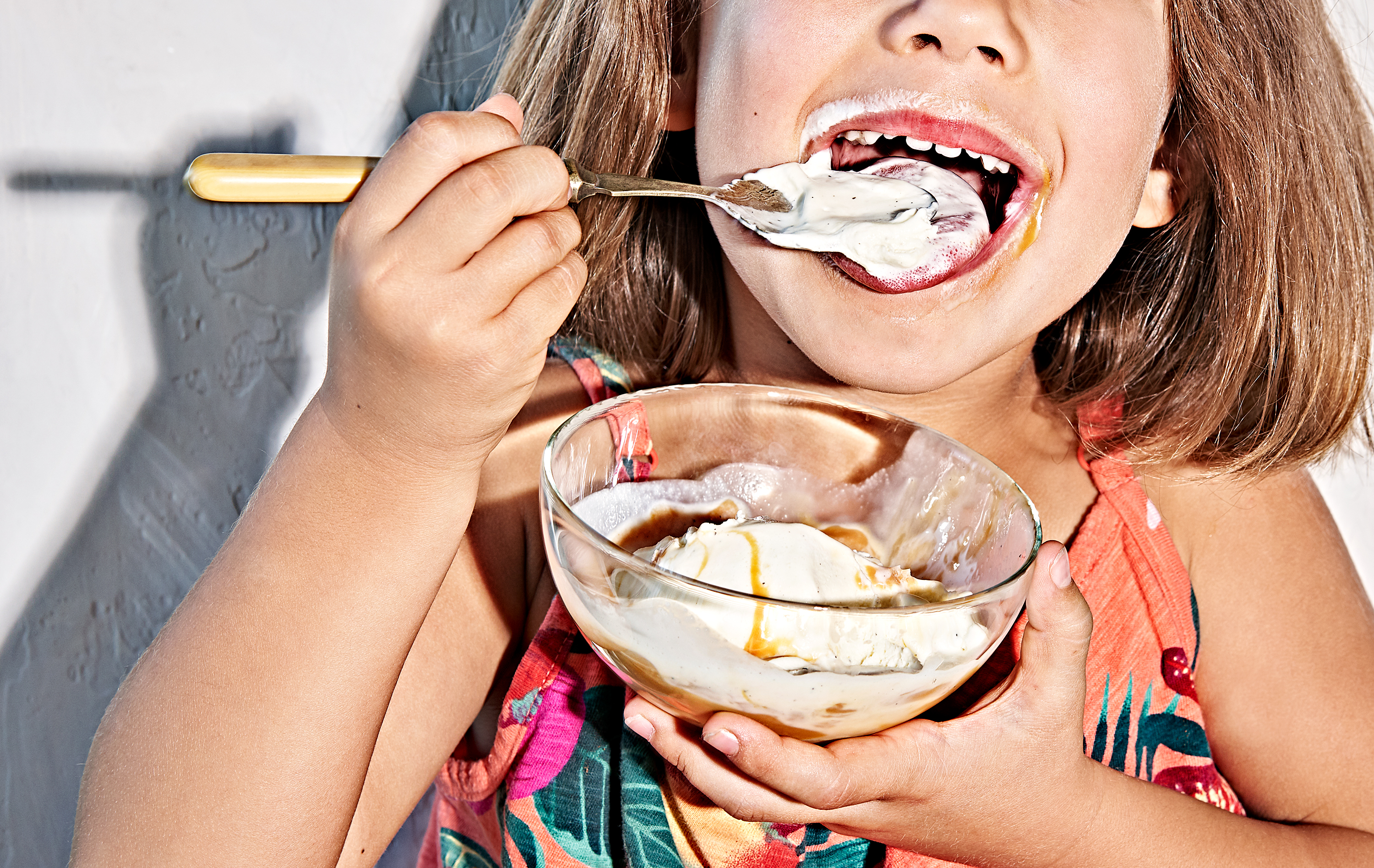Young girl eating ice cream with dulce de leche caramel.