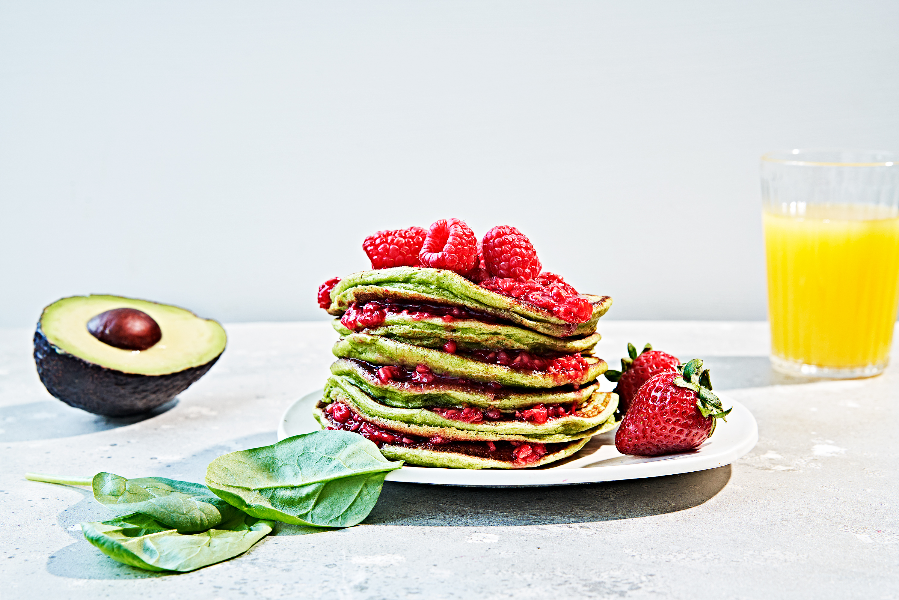 Stack of green monster pancakes made with spinach and topped with raspberries.